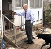 "The Stevens household is home base to three dogs and three ""outdoor"" cats. Phil Stevens is greeted by dogs Shy Guy, left and Sonny."