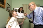 """Dr. Phil,"" as many of his patients call him, checks out the throat of fourth generation patient Danielle Irwin while her mother Elizabeth watches the proceedings."