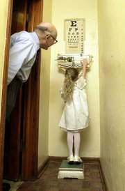 Danielle Irwin, 5, tries on tiptoes to reach the sliding weight on the old set of scales in Dr. Phil Stevens' Tonganoxie doctors office. The scales belonged to Phil's father, Dr. Delos Stevens, and were used in his Oskaloosa office. Danielle is the daughter of Steve and Elizabeth Irwin.