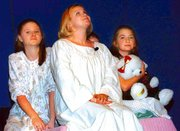 Singing through a thunderstorm, the new governess, Maria (Courtney Hoffhines), comforts the children. From left are Heather Melchior, Courtney Hoffhines and Hillary McPherson.