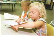 Danielle Rohr and James Paine test their skills with scissors and paper while attending the pre-kindergarten summer session.