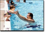 David Rawls encourages his daughter, Megan, 2, to jump in during a day outing to the Tonganoxie swimming pool. The local pool is celebrating its 75th birthday this year.