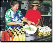 Surrounded by freshly made bottles of tomato vinaigrette, honey dijon mustard and cucumber pickles, Cathy Hawes, left, and Betsy Faubion pack green beans into sterile jars. The women grow much of the produce that they can at Doolittle Farms, and the remainder is obtained from area growers.