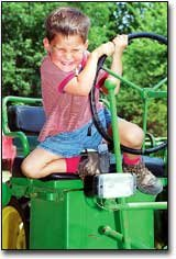 Mark Nickels, 3, who lives in McLouth, grimaces as he attempts to climb down from the seat of this John Deere tractor.