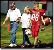 Debby Kay and Bill Altman walk with Willie Altman before Thursday's senior night football game.