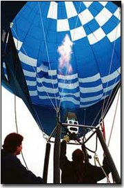 Preparing for liftoff, Danny Mathia operates the burner on his hot-air balloon Friday before takeoff south of West Haven Baptist Church on U.S. 24-40 Highway as Beckie Borella, assists.