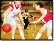 Tonganoxie girls basketball players Tricia Ridenour, left, and Erin O'Brien, right, work on drills as their coach, Leslie Foster, center, watches their techniques. Foster has coached many of the players on the team before, which allows for a family atmosphere among players.