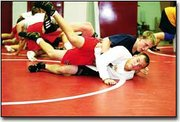 Shann Trieb tries to stay on top of Mike Andrews during wrestling practice last week at Tonganoxie High School. The team's first meet is a junior varsity meet at 9 a.m. Saturday at Santa Fe Trail.