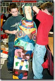 Travis Cook, left, and Zachary Mayse put the finishing touches on one of the mummies sixth-graders at Tonganoxie Elementary School created as part of their study of ancient Egypt.