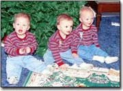 Triplets, from left, Joe, Jake and Jon Derzinski rest beside the Christmas tree that they will soon decorate with the assistance of their sister, Maggie.