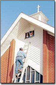 Climbing up a ladder at the McLouth Methodist Church, Richard Eason planned to assist John Kimberlin, in the window, as he checked the church's insulation. Tony Bechard, trustee, said the church attic appeared to have been insulated in the late 1960s with a recycled paper product.