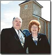 Herman and Waneta Karriker stand in front of the Assembly of God church, which is being rebuilt after the original church was destroyed by a tornado.