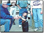 Giving it a quick once-over, Travis Bartlett, who is almost 2 years old, accepts an autographed baseball from former Kansas City Royals pitcher Dennis Leonard at Thursday's grand opening of McLouth High School's baseball and softball season. Travis is the son of Howard and Nancy Bartlett, McLouth.