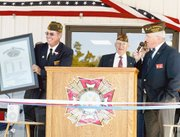 Larry Meadows, post commander of VFW Post 9271, holds the new copy of the VFW's charter. Jefferson Lawson, state commander of Kansas VFW, presented the charter to the group during Saturday morning's dedication of the new post home. The building's construction, which began two years ago, was recently completed.