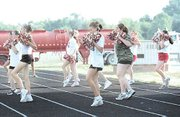 Drill team members practiced their routines Friday morning near a water truck that was delivering water to be sprayed on Tonganoxie High School's Beatty Field.