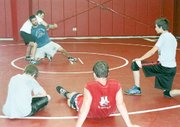 Jeff Sylvester and Gabe Re demonstrate a move to campers at last week's Tonganoxie wrestling camp.